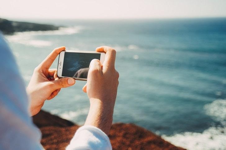 携帯で写真を撮っている場面