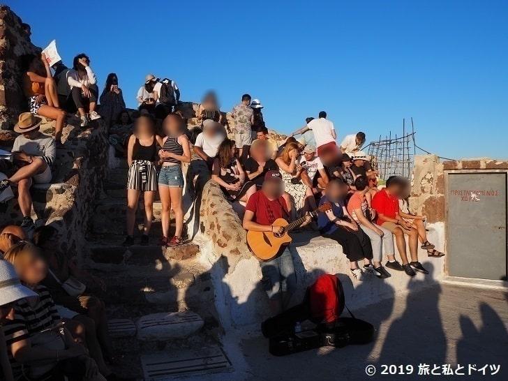 イアの古城で夕日待ちをする人々