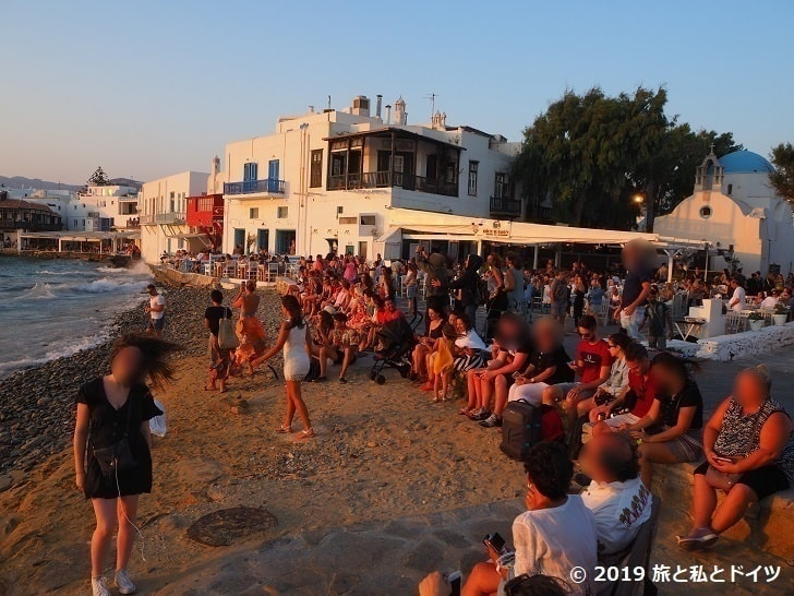 カトリミの風車下広場で夕日待ちをする人々